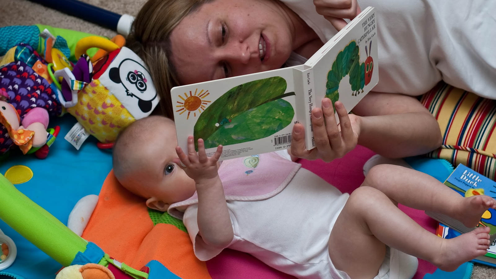 mom reading board book to baby