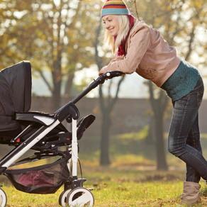 nanny pushing stroller at the park
