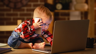 toddler playing on smartphone and laptop