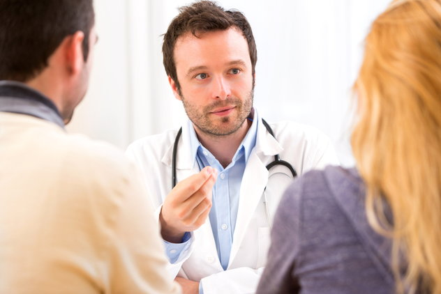 A doctor meeting with a man and a woman.