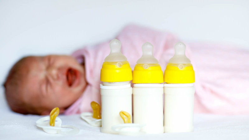 Baby crying with baby bottles