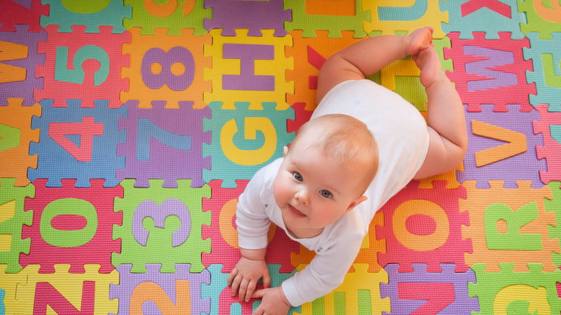 Baby on alphabet mat looking up