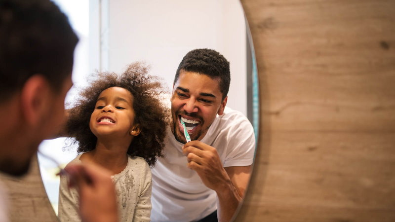 dad brushing his teeth with his daughter