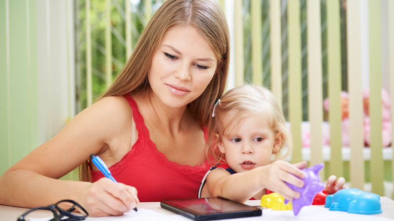 mom writing a budget with baby on her lap