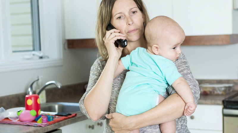 mom holding baby while talking on the phone