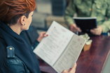 Woman in recovery reading a restaurant menu riddled with alcoholic beverages
