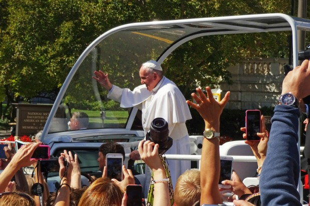 the pope standing on a vehicle while waving at sea of people