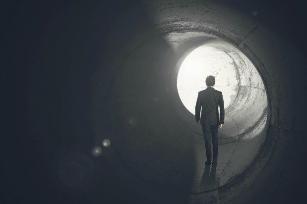 man walking towards light at the end of the tunnel