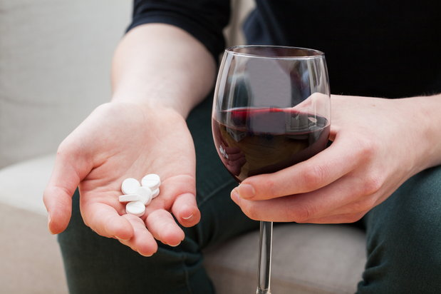 wine glass and pills in hand