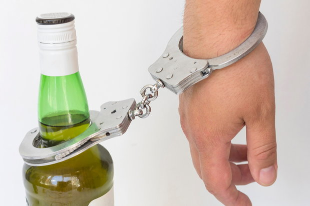 alcoholic handcuffed to a bottle of liquor