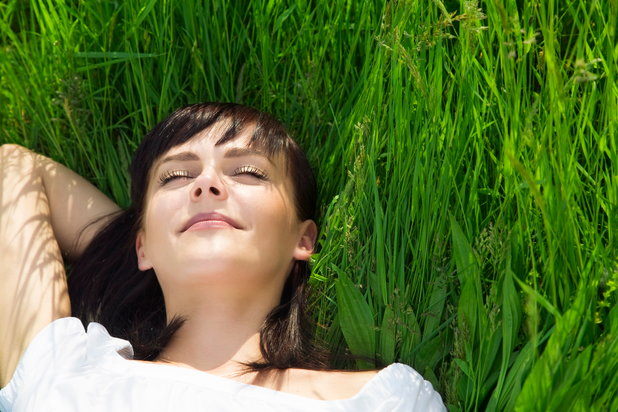 A woman lies in the grass feeling happy with the benefits she's experienced staying sober.