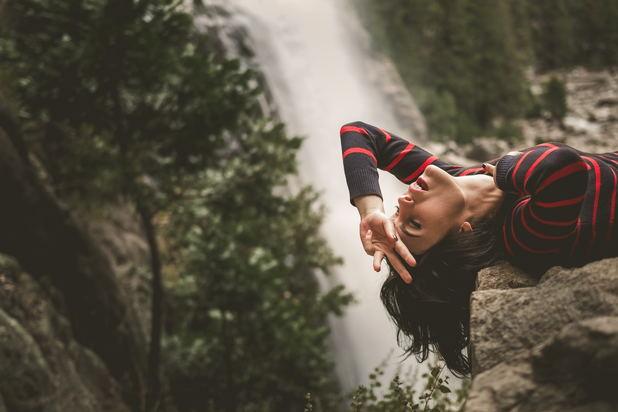 emotionally free woman laying near waterfall
