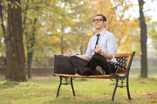 Man in suit meditates on a park bench