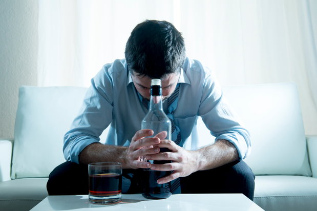 man in business attire drinking with head down