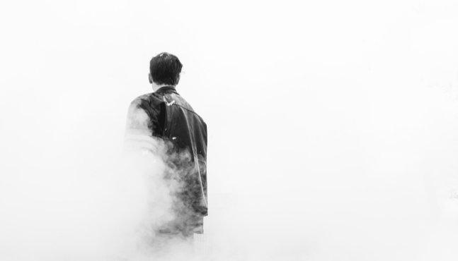 man walking through cloud of smoke
