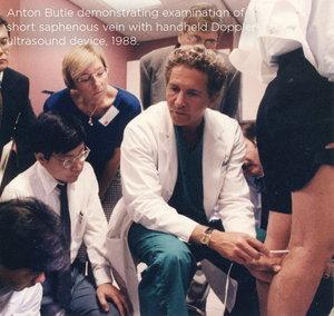 Anton Butie demonstrating examination of the short saphenous vein with handheld Doppler ultrasound device, 1988.