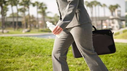 A working mom holding a briefcase and a bottle.