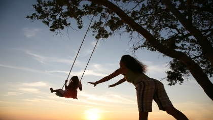 A mom pushes her daughter on a tree swing.