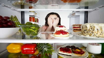 A woman is tempted by a cake in her fridge.