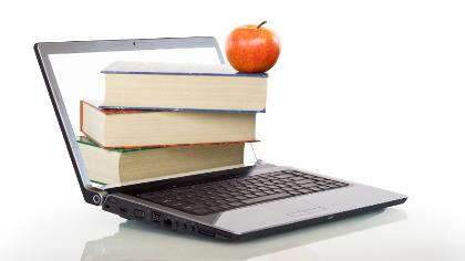 An open laptop with books and an apple.