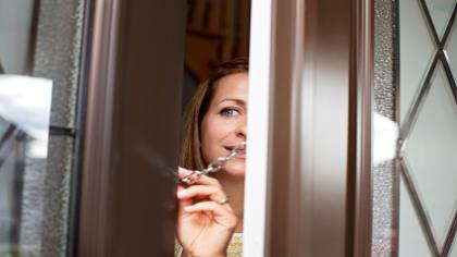 A woman peeks around the front door to see who's there.