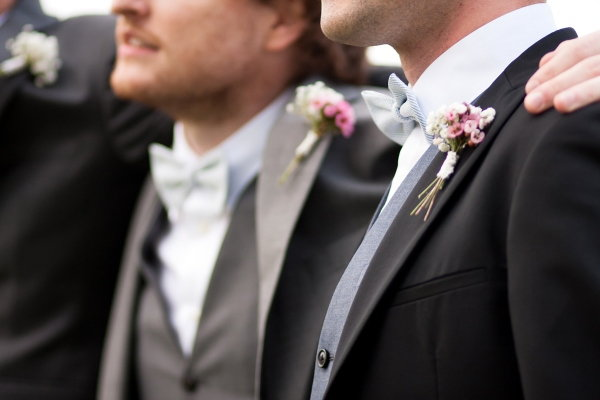 A group of groomsmen wearing pink flower boutonnieres.