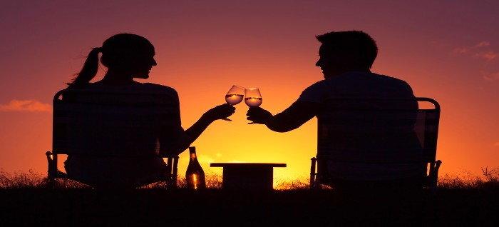 couple enjoying sunset with beverage