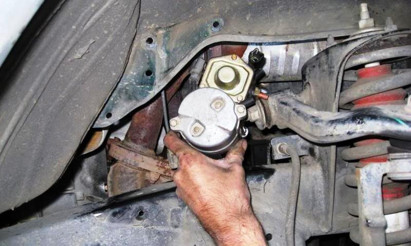 Rotate the starter, disconnect the electrical wiring, and take out through the wheel well