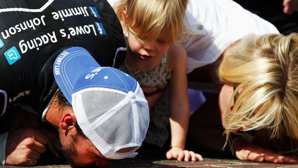 Jimmie, Genevieve Marie and Chandra Johnson kiss Indy's bricks - NASCAR photo