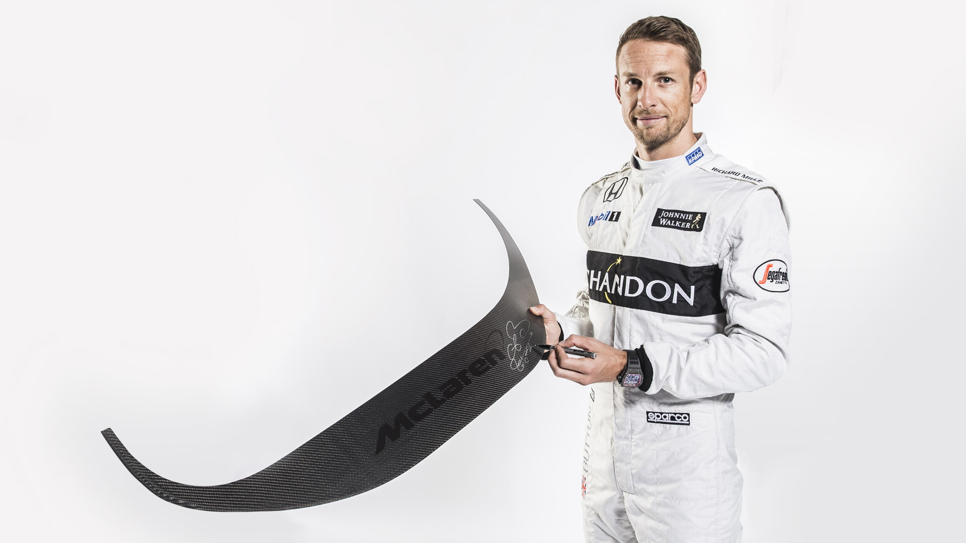 Jenson Button with the signed door sill of the McLaren 675LT Coupe to be auctioned